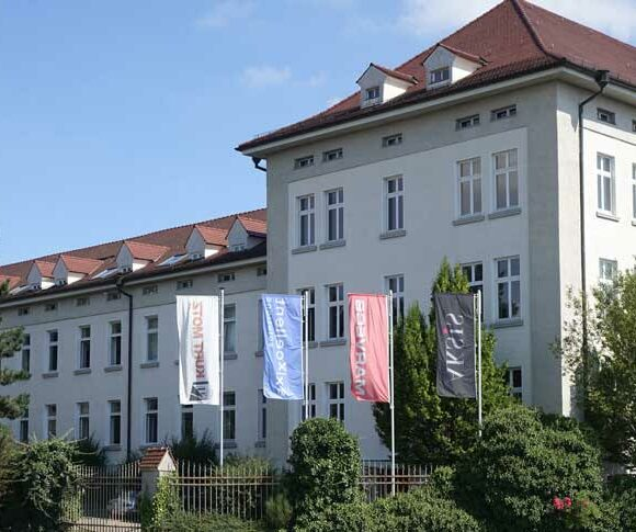 Insights - Wehende Fahnen vor dem Gebäude der Aksis Werbeagentur mit dem Logo