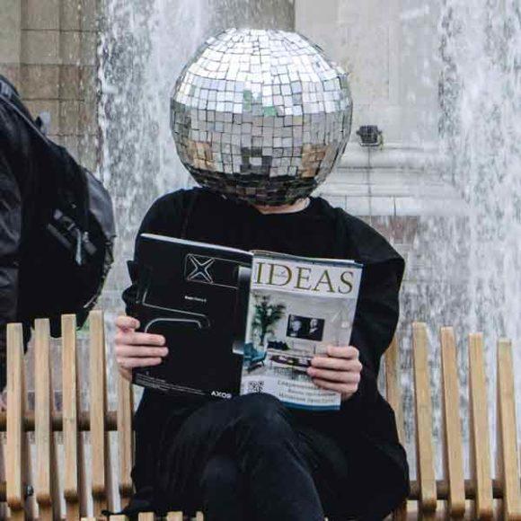 Insights - Eine Person mit einer Diskokugel auf dem Kopf liest ein Magazin