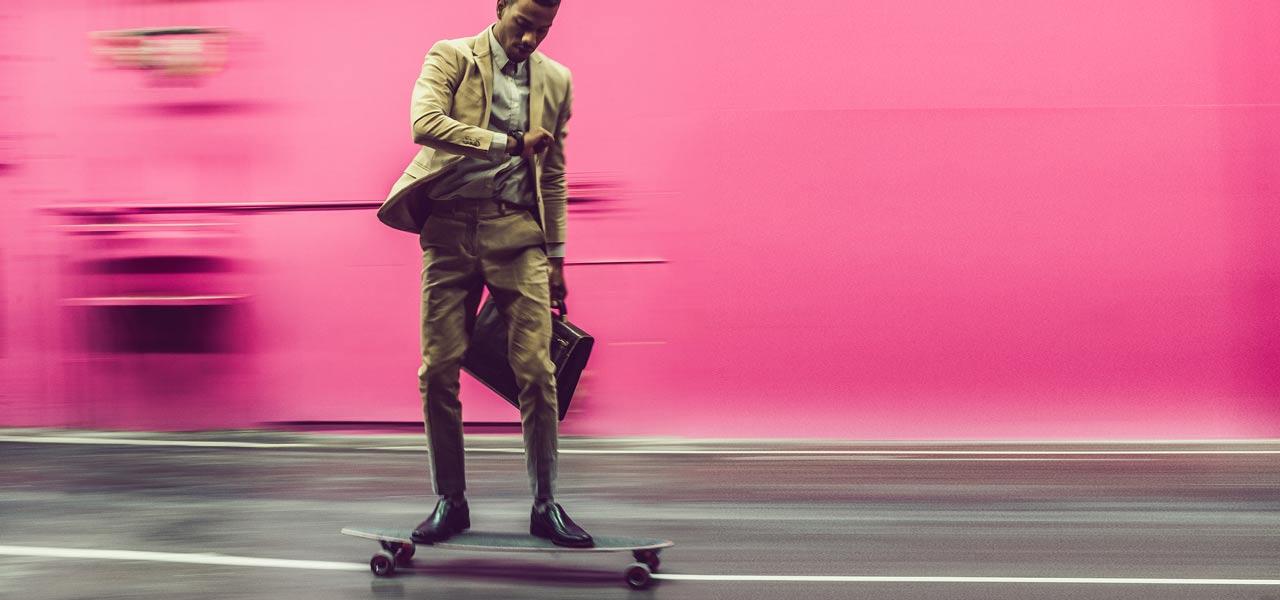 Ein Mann mit Anzug fährt schnell auf seinem Skateboard und schaut dabei auf die Uhr