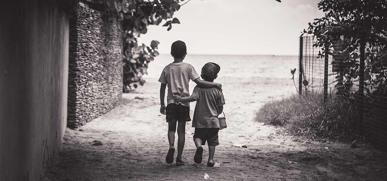 Zwei Kinder gehen Arm in Arm Richtung Strand, Schwarzweiß