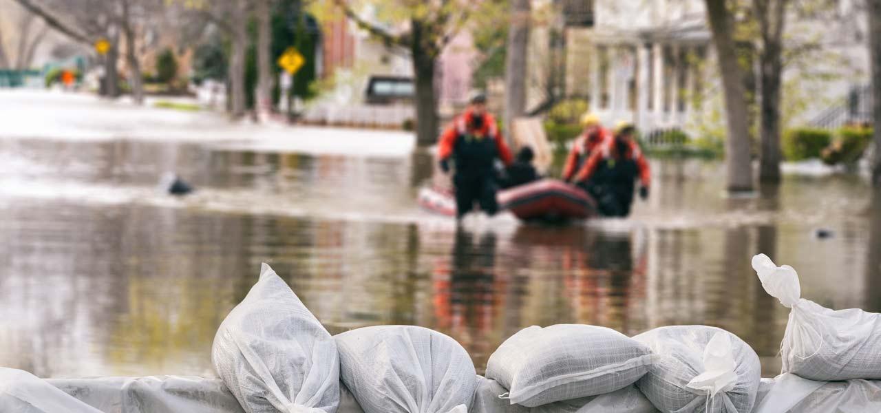Sandsäcke halten die Flut auf, auf dem Wasser fährt ein Boot. Deutsche Traumastiftung
