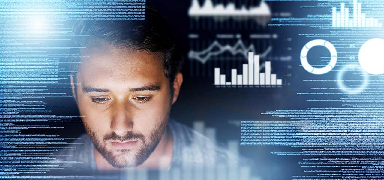 Ein Mann arbeitet am Computer, um ihn herum ist blaues Licht und holografische Diagramme