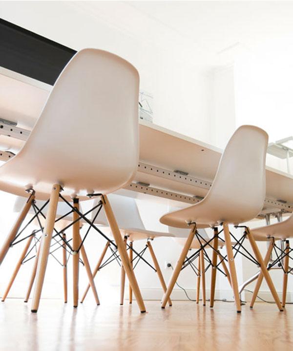 Untersicht auf mehrere Stühle, die an einem Tisch stehen. Du suchst einen Job in der Aksis Werbeagentur Ulm?
