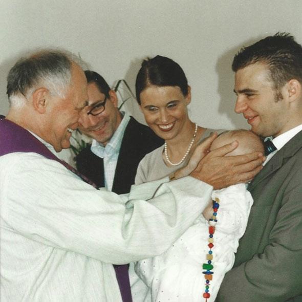 Klaus Stock berührt den Kopf eines Kindes bei einer Taufe
