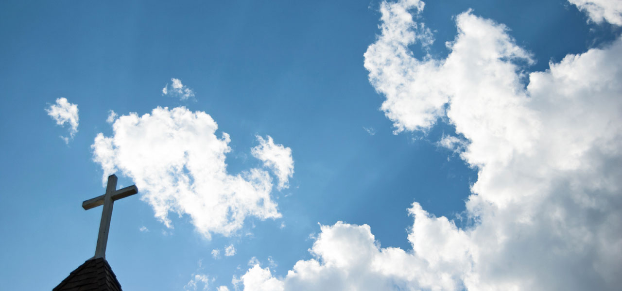 Die Spitze eines Kirchturms mit Wolken