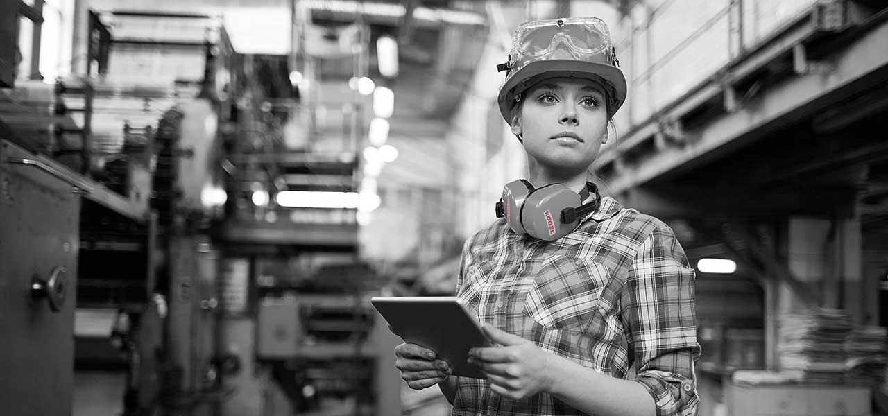 Schwarzweißbild einer Arbeiterin in einer Fabrikhalle