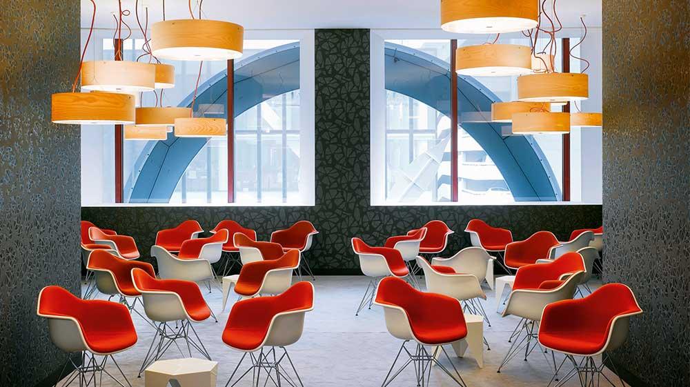 Mehrere Stühle stehen an kleinen Tischen unter Lampen