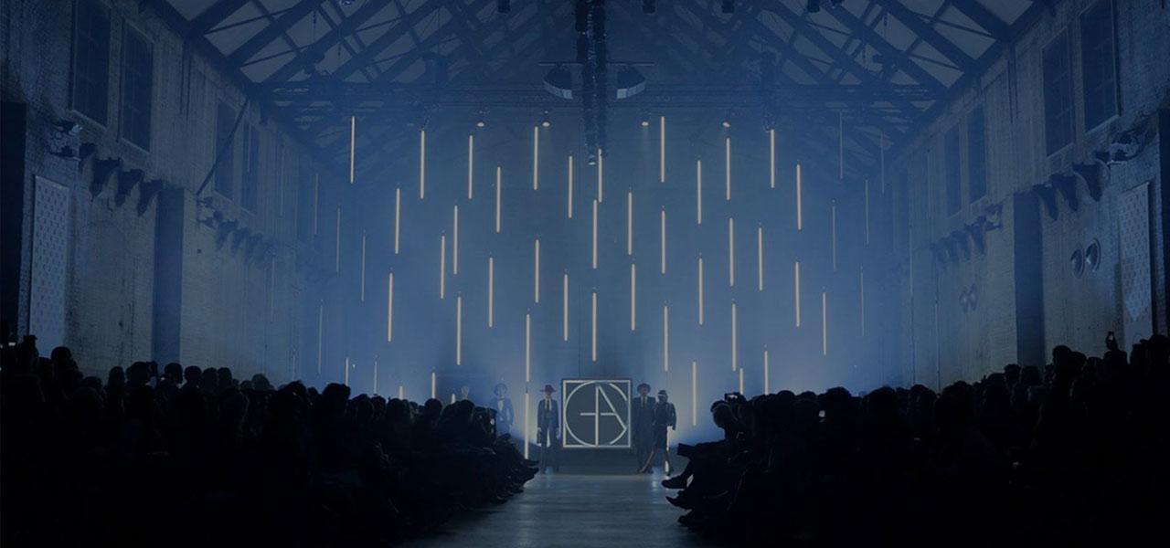Ein Laufsteg in einer Lagerhalle, an der Rückwand hängen Neonröhren