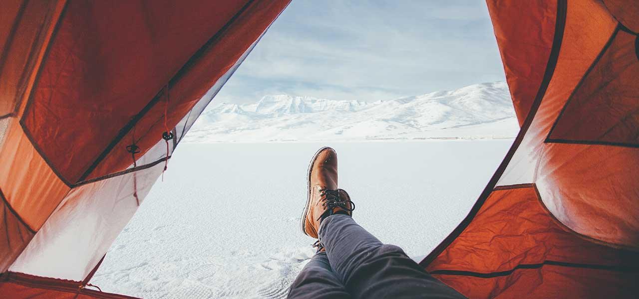 Jemand liegt in einem Zelt in einer Schneelandschaft und streckt die Beine aus der Öffnung
