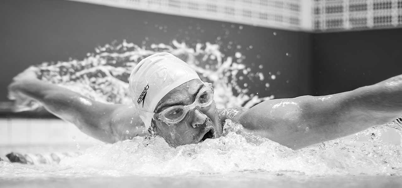 Ein Schwimmer bricht durch die Wasseroberfläche beim Brustschwimmen und holt Luft