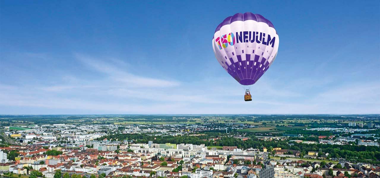 Ein Ballon fliegt über eine Stadt. Darauf das Logo des 150 jährigen Stadtjubiläums der Stadt Neu Ulm