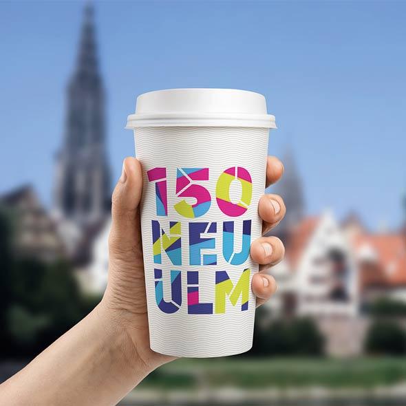 Kaffeebecher mit dem entworfenen 150-Jahre-Neu-Ulm Schriftzug. Konzipiert von der AKSIS Werbeagentur