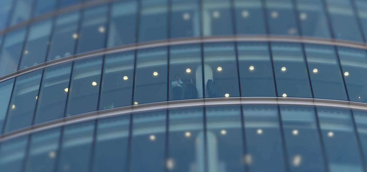 Ein Bürohaus von unten mit verglaster Front. Eine Person, die am Fenster steht ist erkennbar