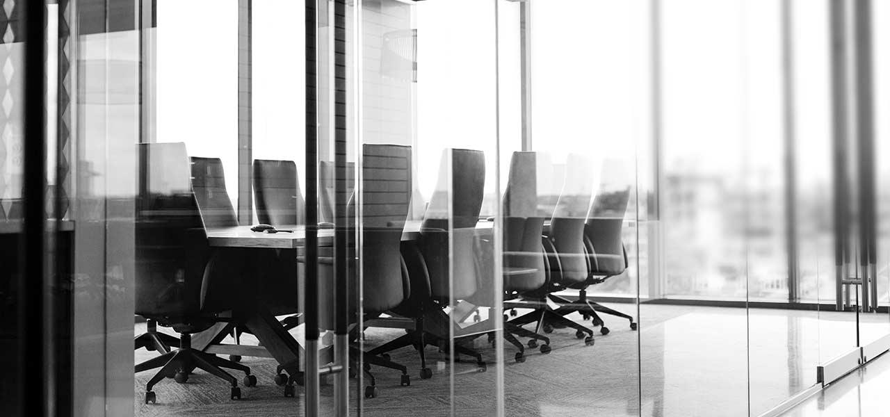 Ein Konferenzraum mit einem langen Tisch an dem viele Bürostühle stehen