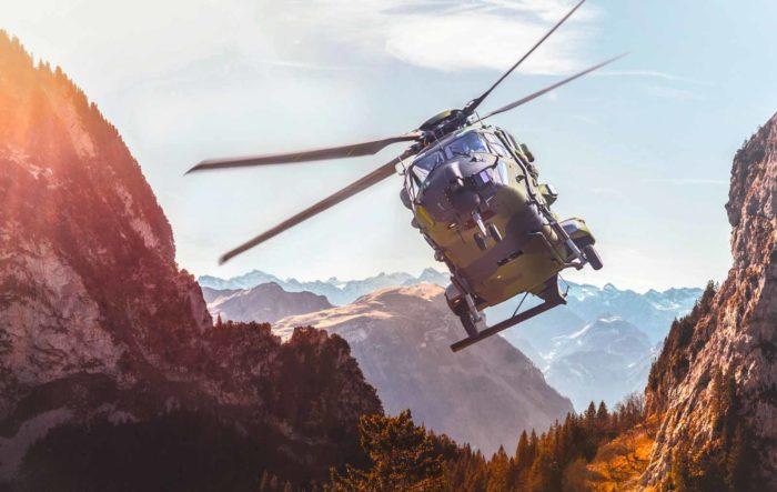 Ein Hubschrauber fliegt durch eine Berglandschaft. Bild von der Website von Spherea Germany