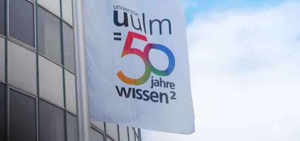 Wehende Fahnen vor der Universität Ulm mit dem Logo der Uni Ulm 50 Jahre Wissen
