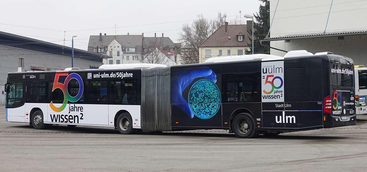 Die Beklebung des Busses der SWU in Ulm mit dem Logo und Bildern der Uni Ulm – 50 Jahre Wissen