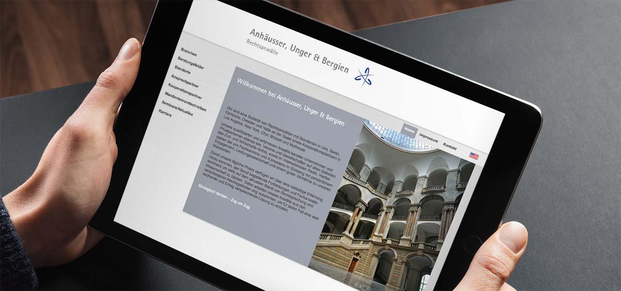 Ein Tablet, dass von 2 Händen gehalten wird, zeigt die Website der Anhäusser, Unger & Bergien Rechtsanwälte