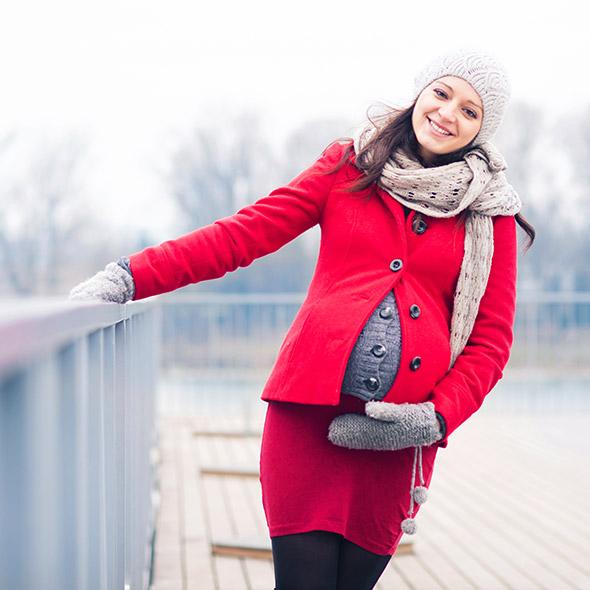 Eine schwangere Frau hält ihren Bauch und ist glücklich