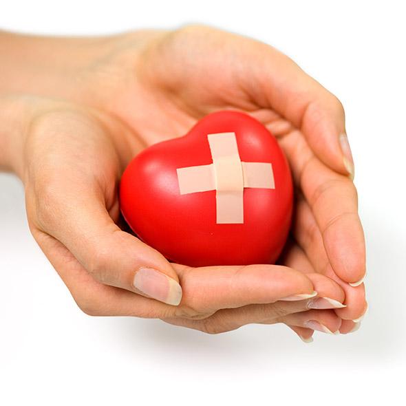 Ein Steinherz wird von Händen gehalten, auf dem roten Herz klebt ein Pflaster