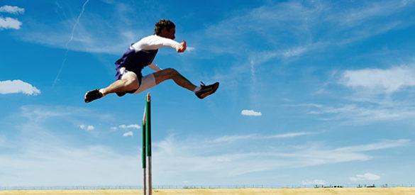 Ein Mann springt über eine Hürde, hinter ihm ist blauer Himmel