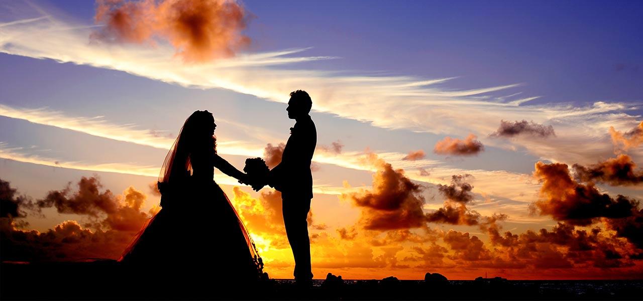 Ein Brautpaar steht vor dem Sonnenuntergang