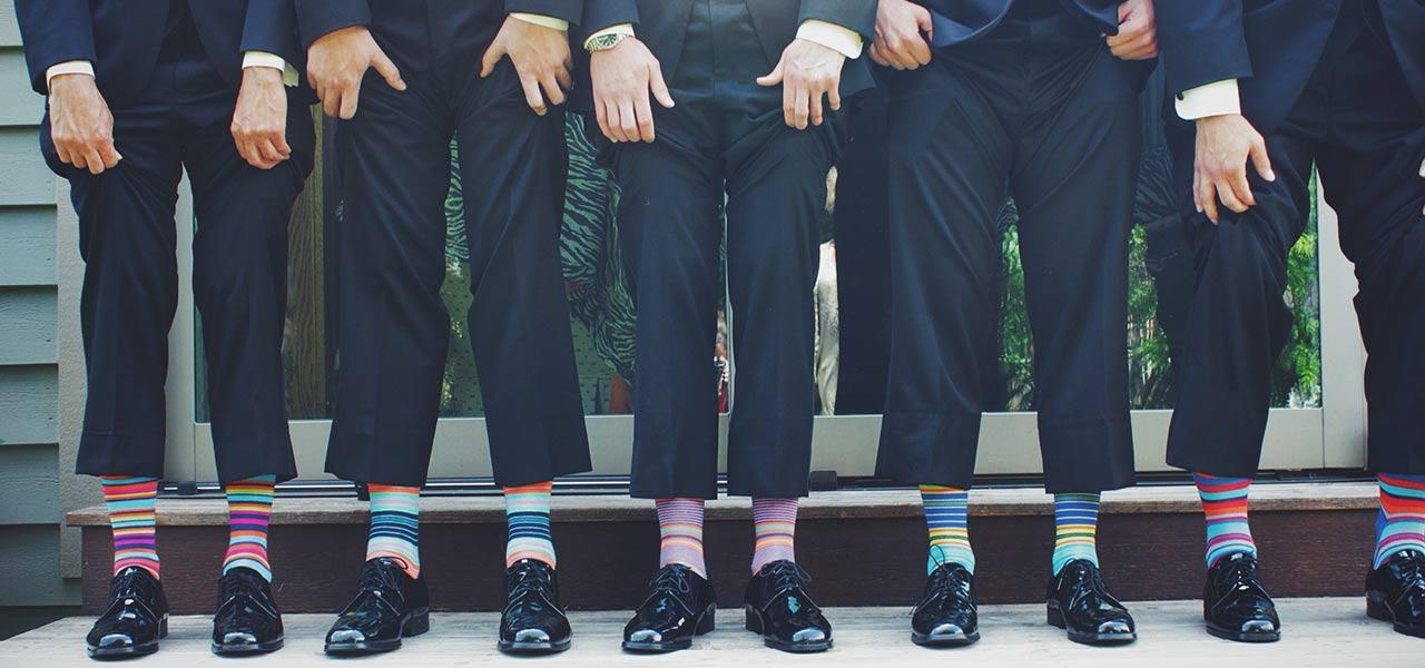 Auf einer Hochzeit: 5 Männer, ziehen ihre Anzughosen hoch und zeigen ihre Ringelsocken.