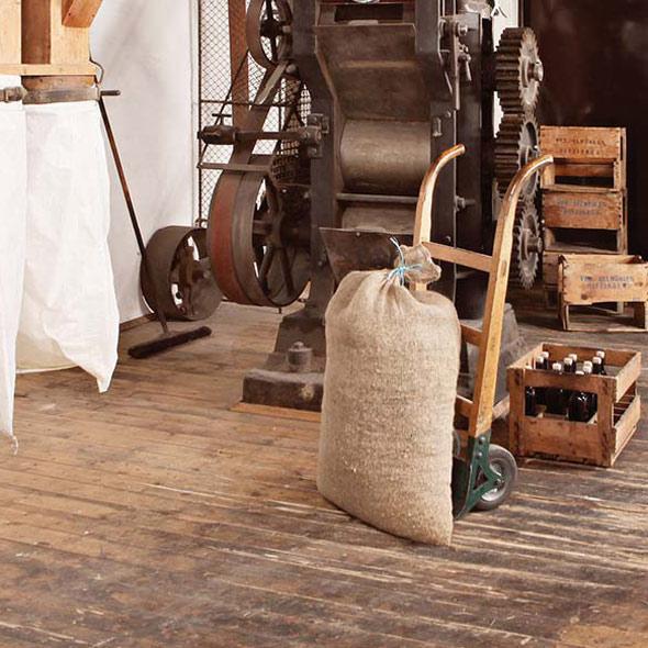 Ein Sack steht auf einer Sackkarre vor einer Ölpresse der Ölmühle Ditzingen