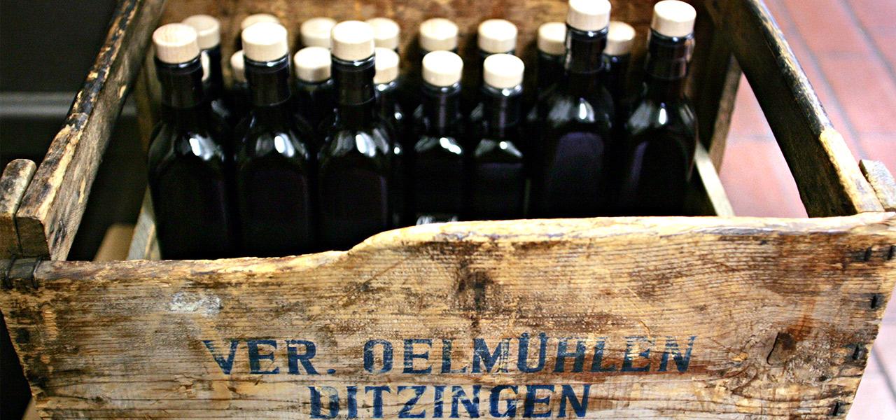 Ölflaschen in einer alten Holzkiste auf der Ölmühle Ditzingen steht