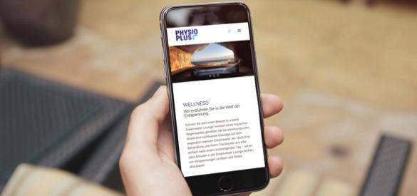 Darstellung der Webseite von Physio Plus auf einem Handy dass von einer Hand gehalten wird.
