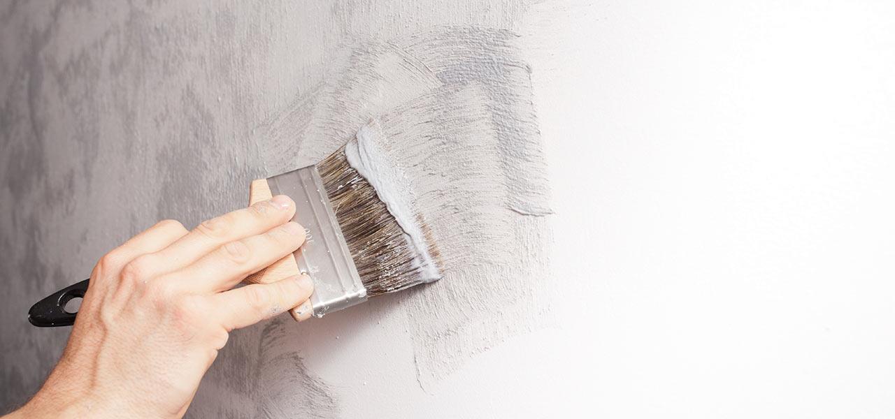 Eine Hand hält einen Pinsel und malt Farbe auf die Wand