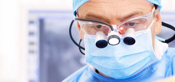 Ein Zahnarzt mit Mundschutz und Brille bei der Arbeit