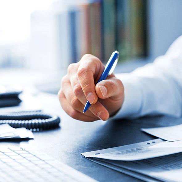 Eine Hand mit Stift schwebt über einem Schreibtisch mit Unterlagen