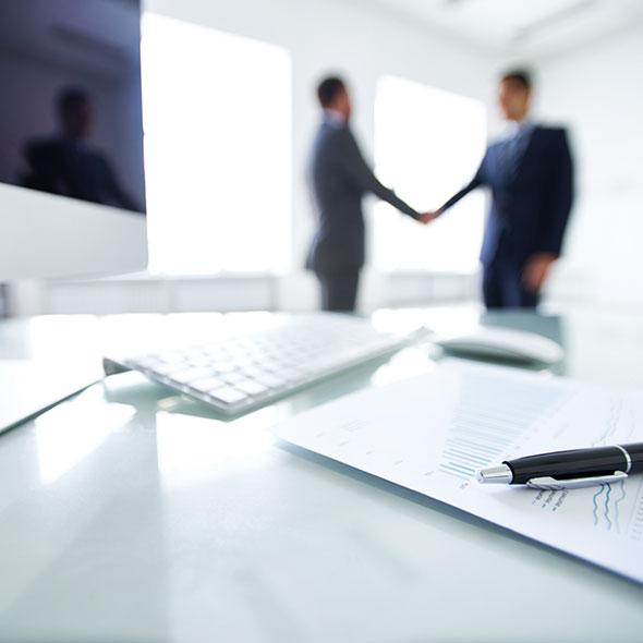 Ein Vertrag liegt auf dem Tisch, unscharf im Hintergrund geben sich zwei Personen die Hand