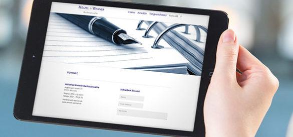 Eine Hand hält ein Tablet auf der die responsive Website von Hoelzel und Wanner zu sehen ist
