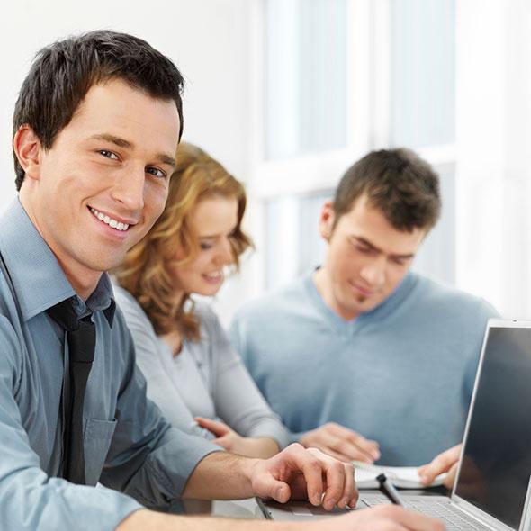 3 Junge Menschen sitzen vor einem Computer. Ein Mann schaut in die Kamera
