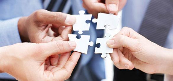 Vier Hände halten jeweils ein Puzzleteil, die vier Teile passen zusammen