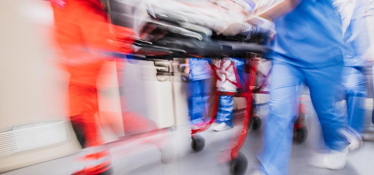 Notfall, ein Ärzteteam trägt einen Patienten durch einen Gang.